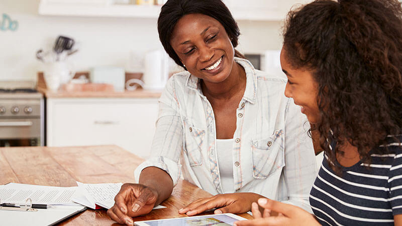 African-American mom helping teenage daughter with school work