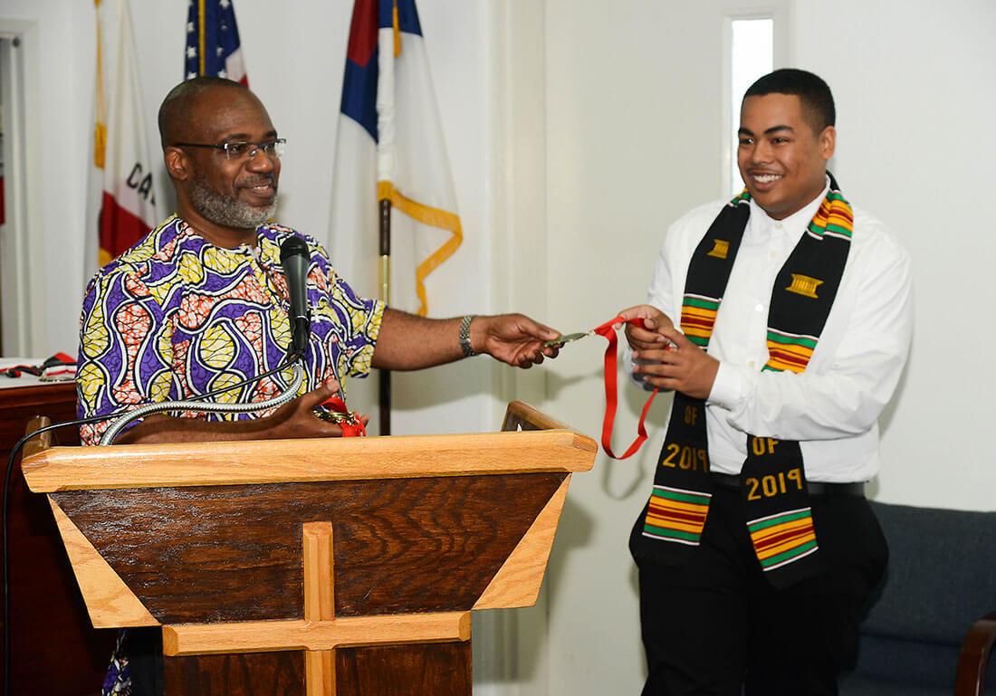 Staff handing student a sash